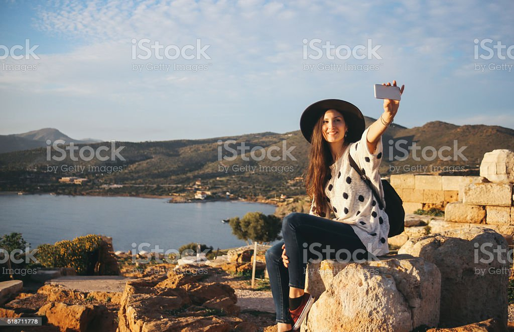 Tourist woman taking a selfie with her smartphone stock photo