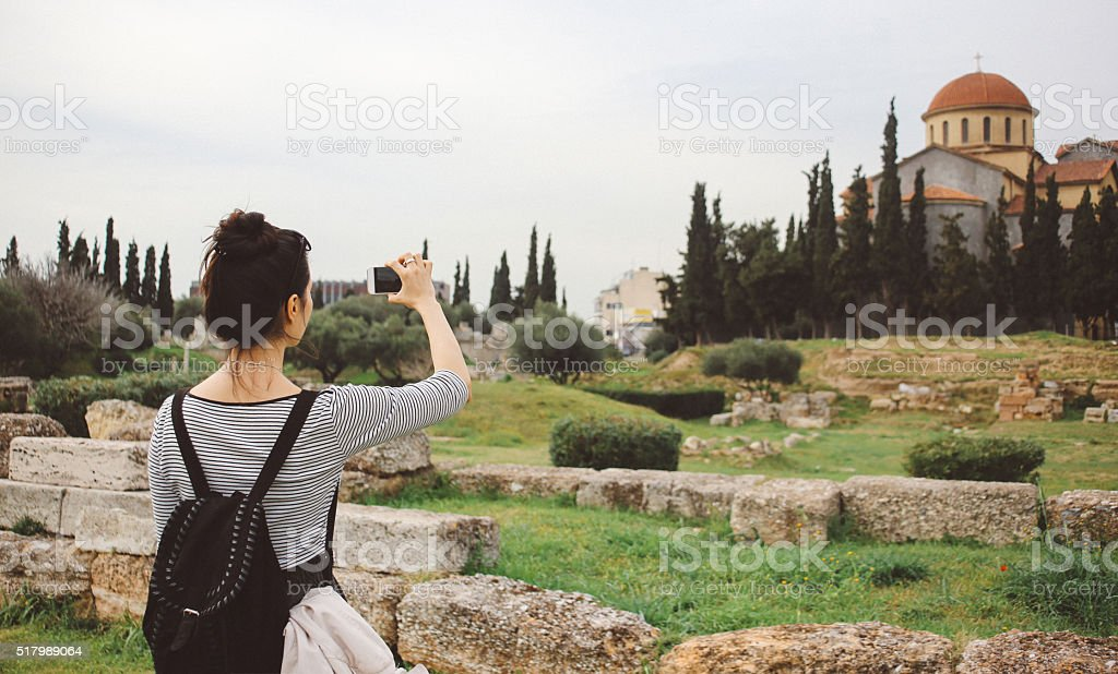 Tourist woman taking photos with her smartphone stock photo