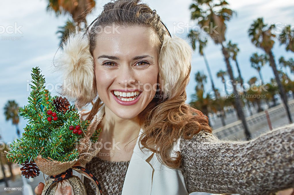 tourist woman taking selfie while holding a little Christmas tre stock photo