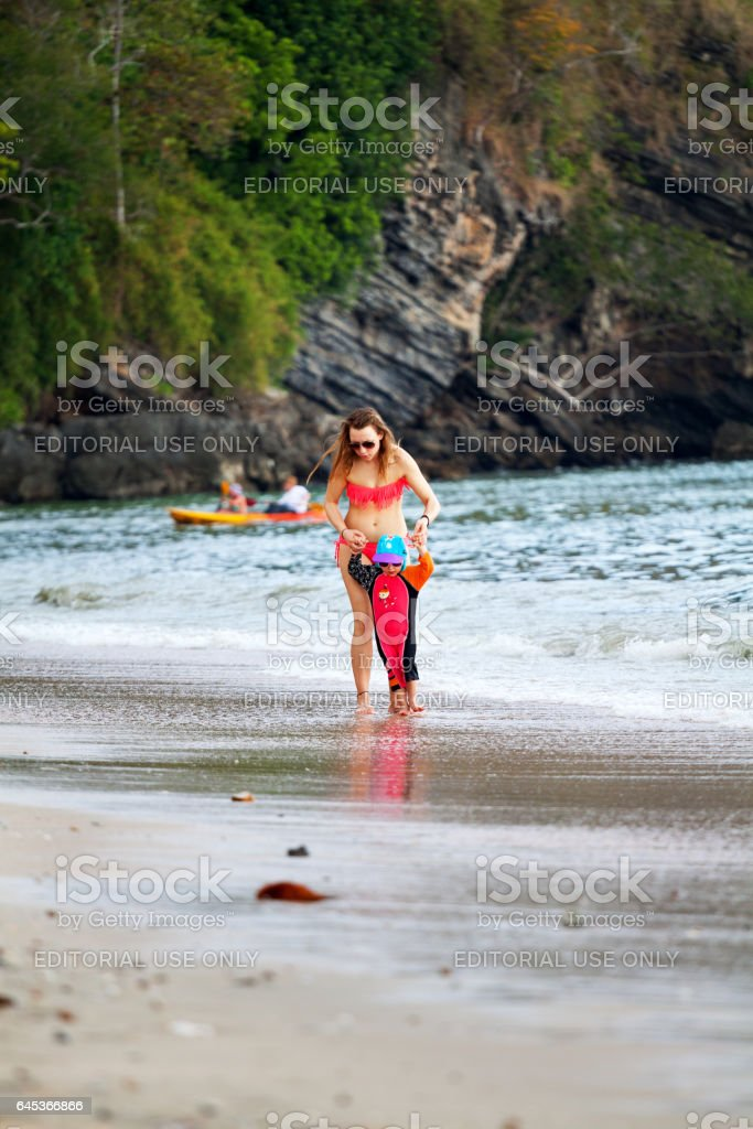Tourist woman with girl in surf at beach stock photo