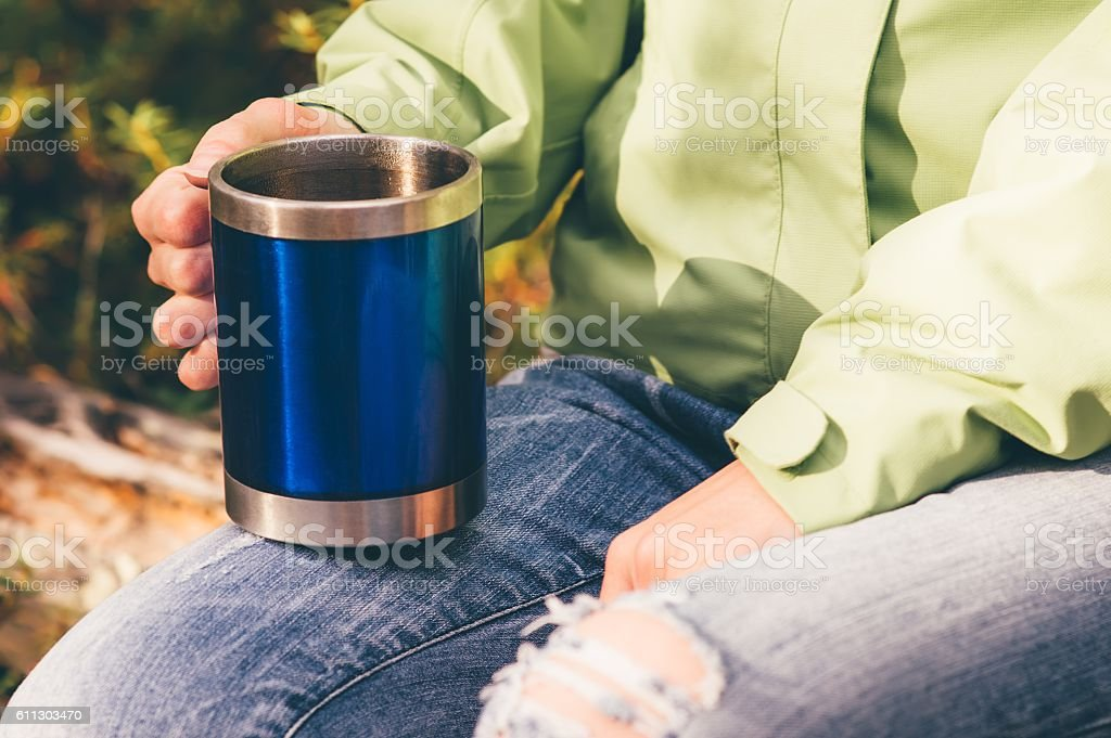 Touristic tea thermal cup in woman hand Travel Lifestyle stock photo