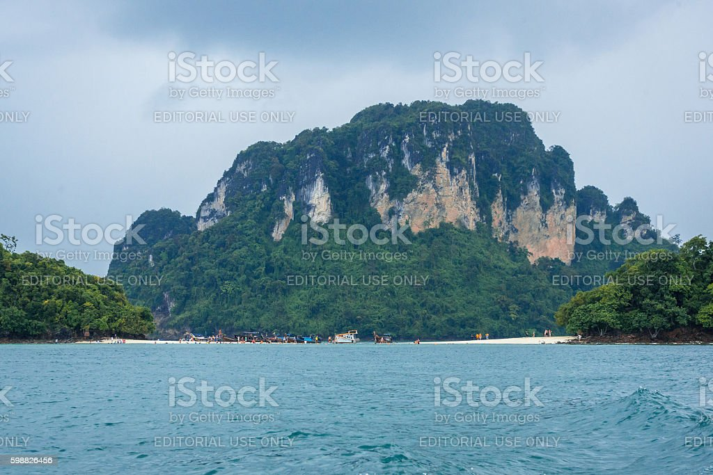 Tourists and boats on small beach with mountain background photo libre de droits