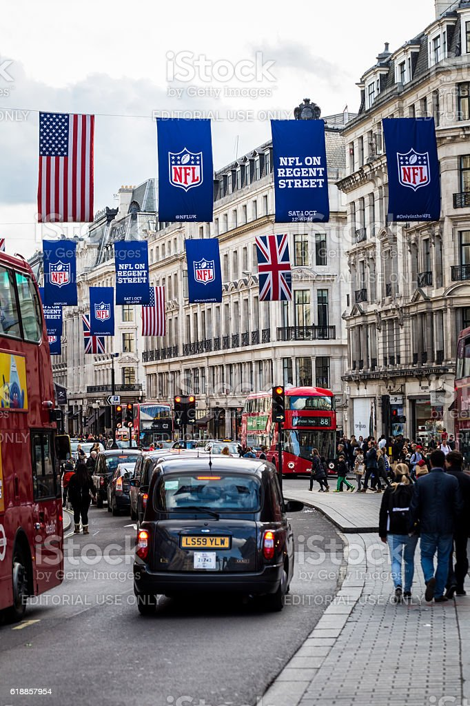 Tourists and buses Regent Street, London, with NFL flags stock photo