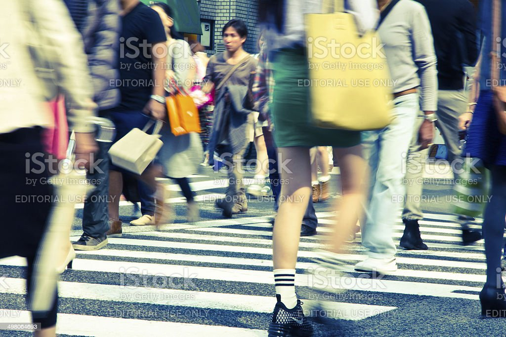 Tourists and business people crossing the street at Harajiku Japan