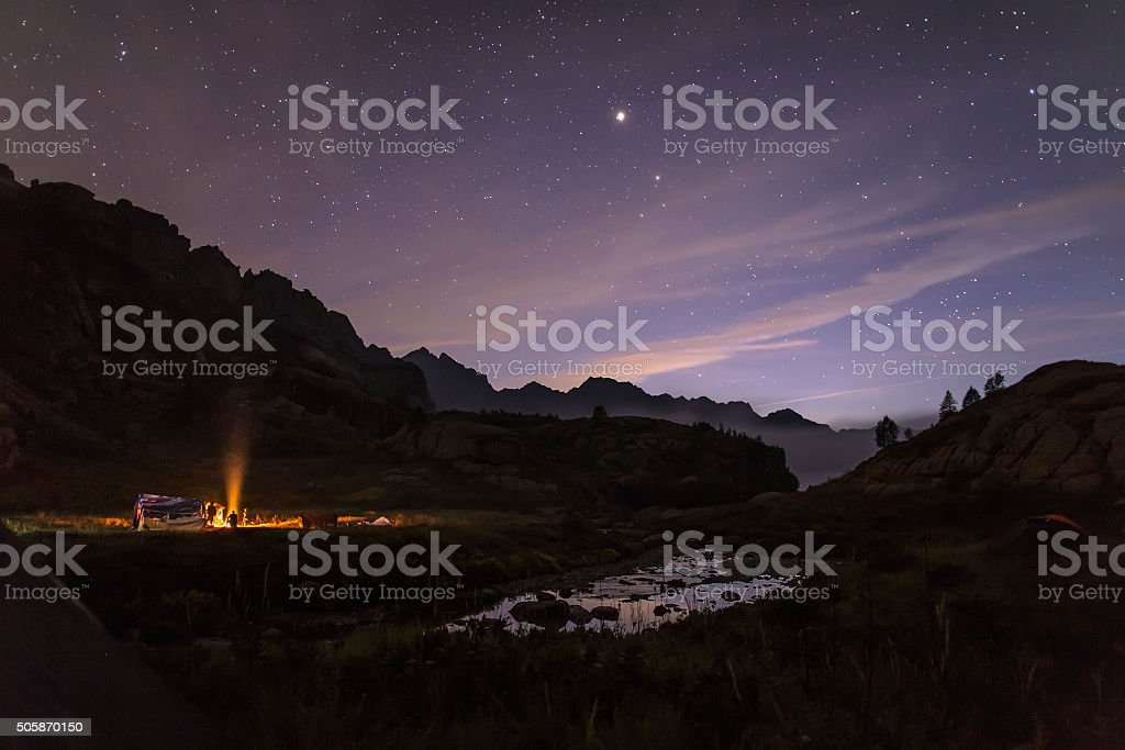 Tourists and hunters are heated around the campfire at night stock photo