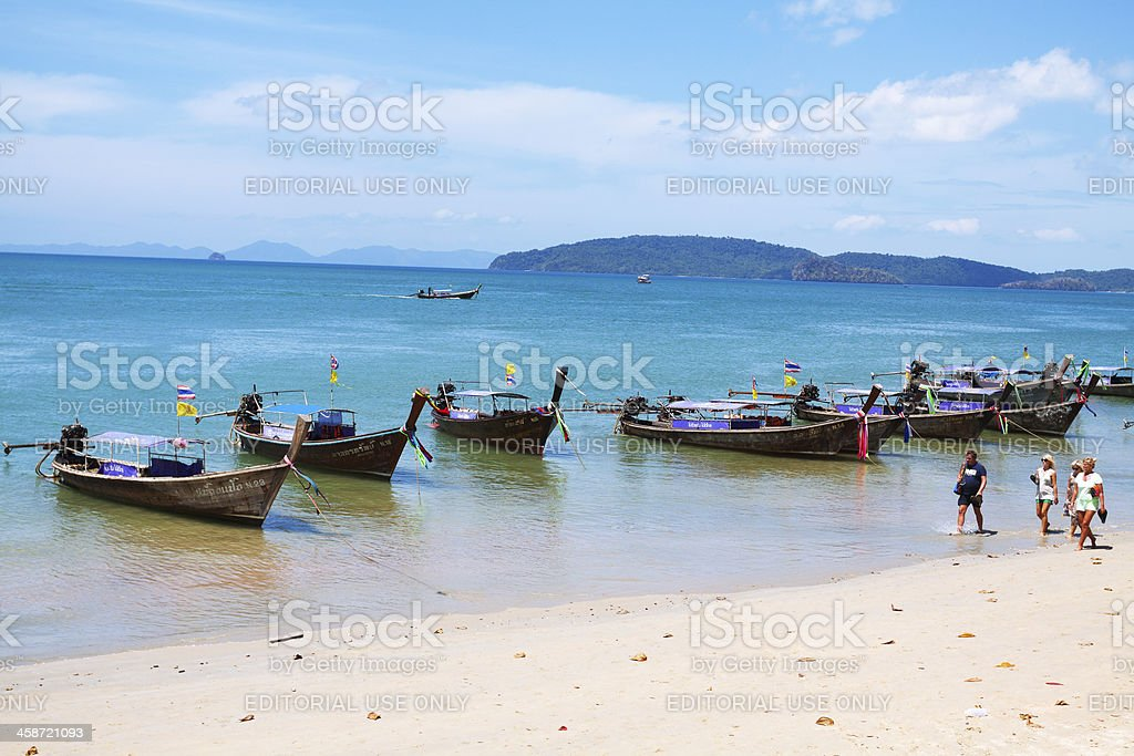 Tourists and longboats at beach royalty-free stock photo