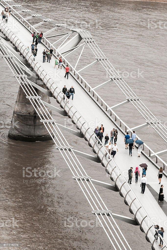 Tourists and Pedestrians walking across Millennium Bridge, London, UK stock photo