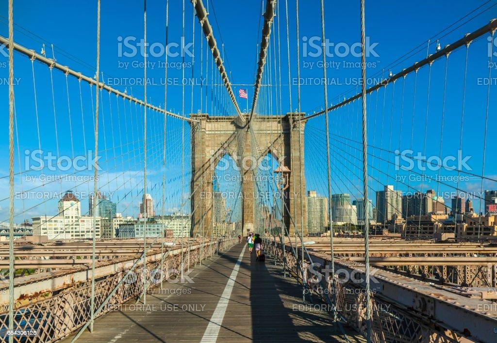 Tourists and residents cross Brooklyn Bridge stock photo