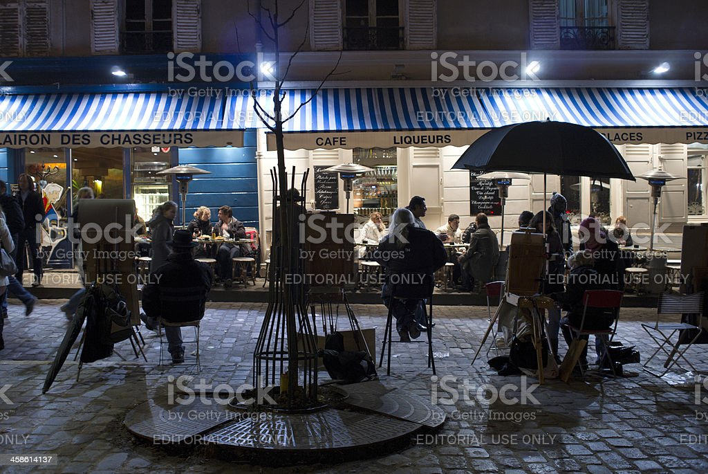 tourists and street artists on Place du Tertre at night royalty-free stock photo