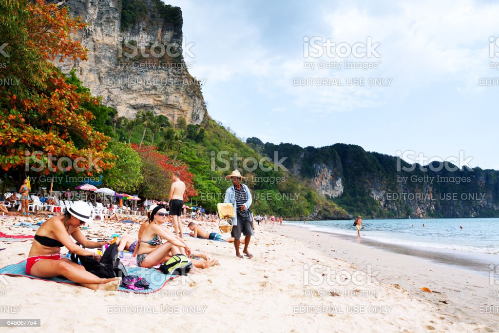 Tourists and thai souvenir vendor on beach of Ao Nang stock photo