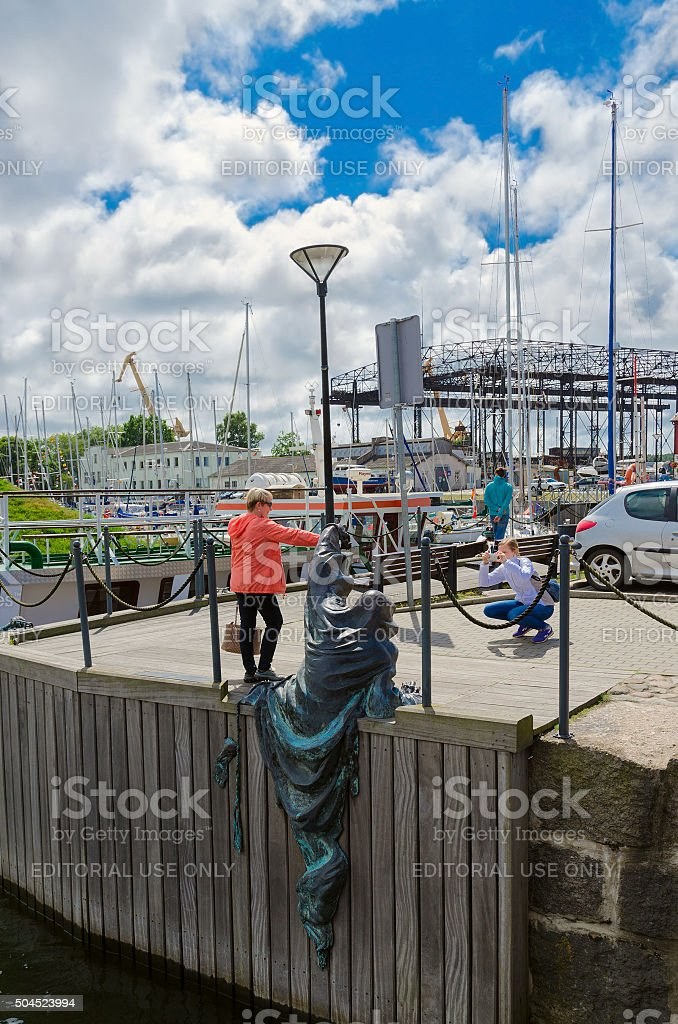 Tourists are photographed near sculpture Black Ghost, Klaipeda, Lithuania stock photo