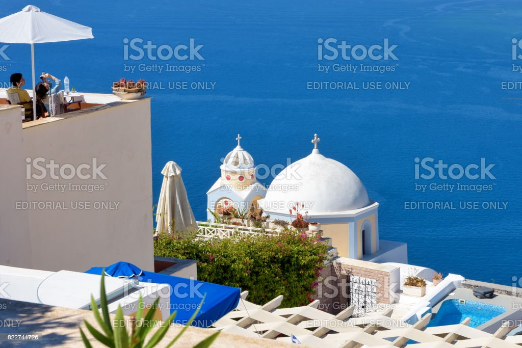 Tourists at a rooftop terrace in Santorini enjoy the view of the blue Aegean sea stock photo