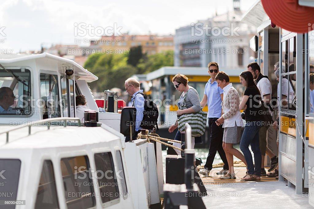 Tourists boarding on the venetian water bus - Vaporetto. stock photo
