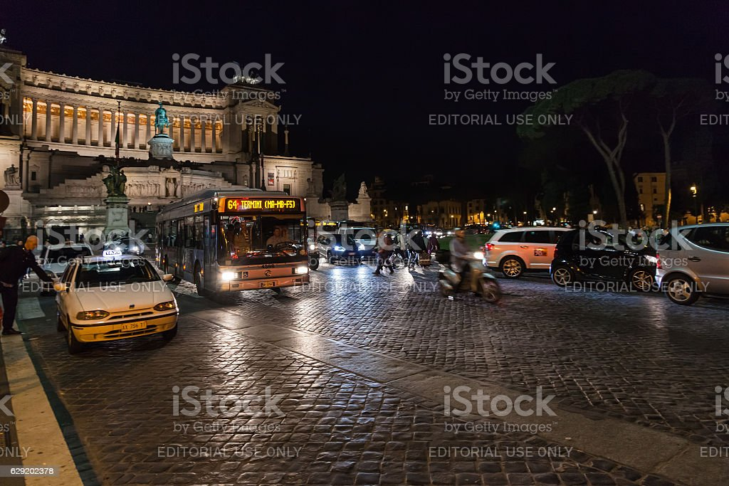 tourists, cars, bus on Piazza Venezia in Rome stock photo