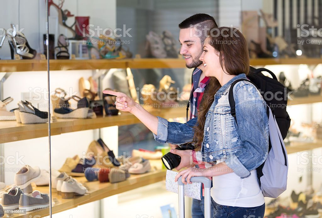 Tourists choosing shoes from showcase stock photo