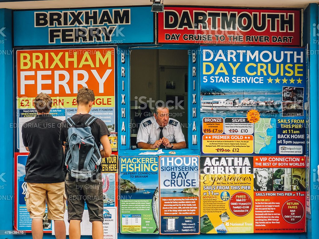 Tourists consider trip options at a Torquay ticket office, UK stock photo
