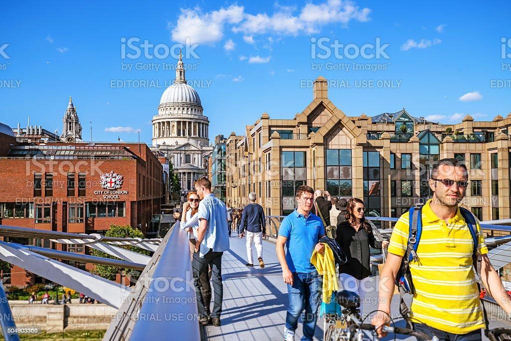 Tourists crossing Millenium Bridge in London stock photo
