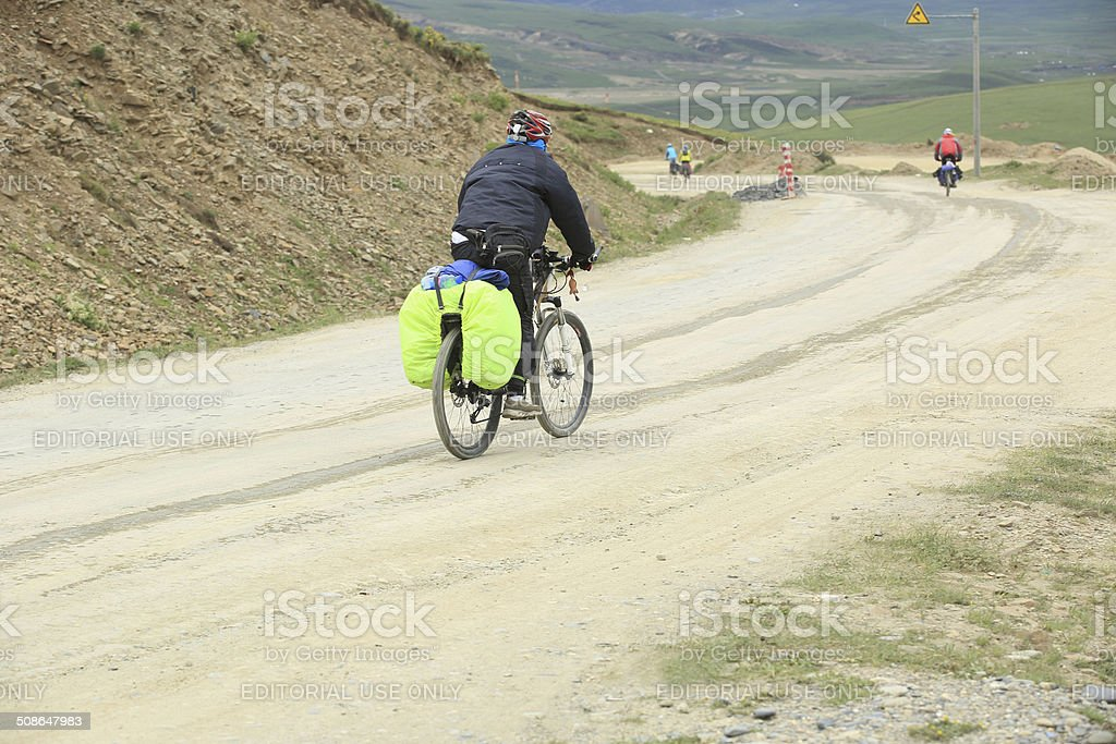 tourists cycling on mountain road to tibet,china stock photo