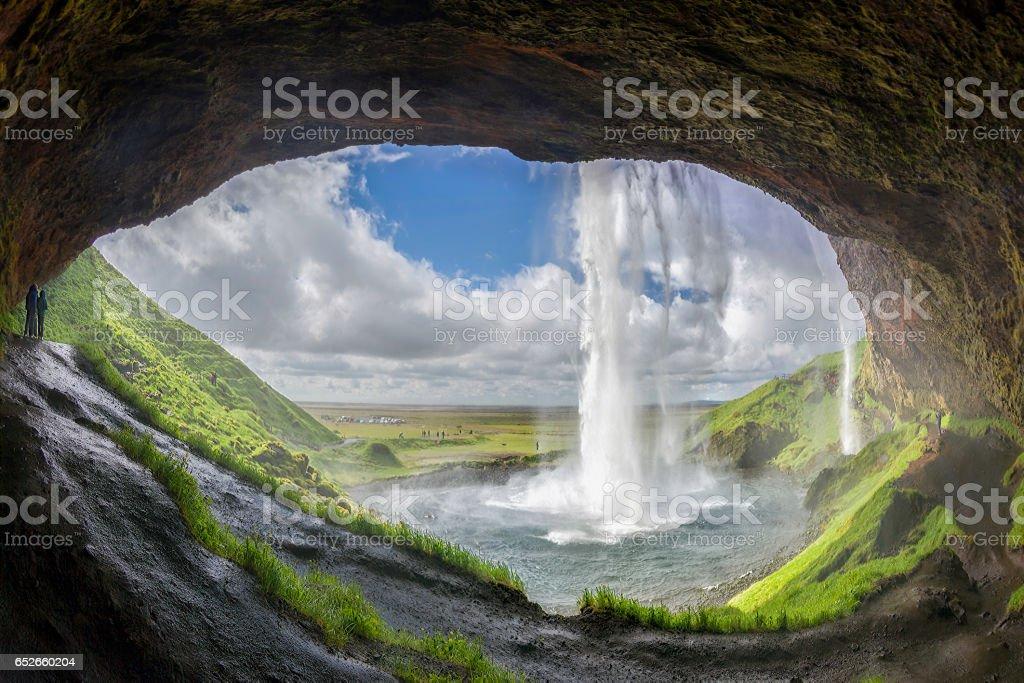 Tourists discover the Seljalandsfoss waterfall stock photo