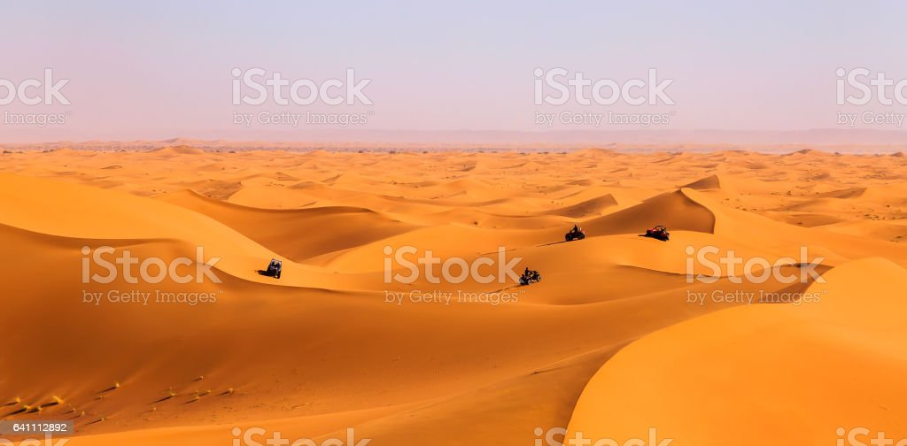 Tourists driving quads and all-terrain vehicles in sahara dunes stock photo