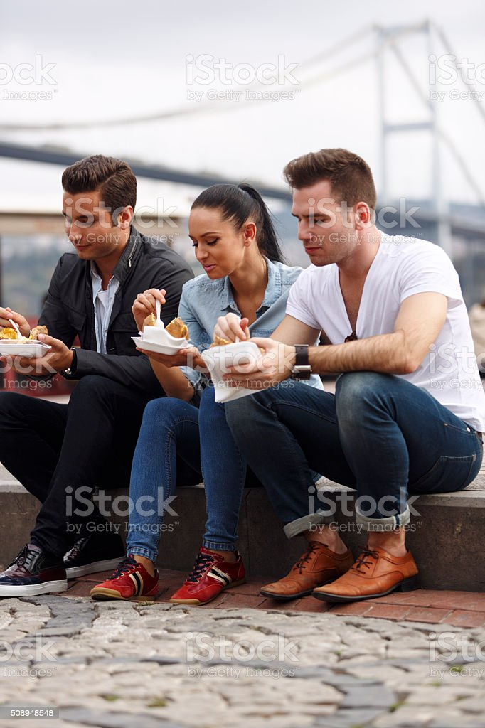 Tourists eating turkish baked potato in Ortakoy, Istanbul stock photo