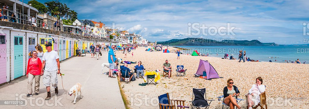 Tourists enjoying busy summer seaside resort Lyme Regis panorama Dorset stock photo