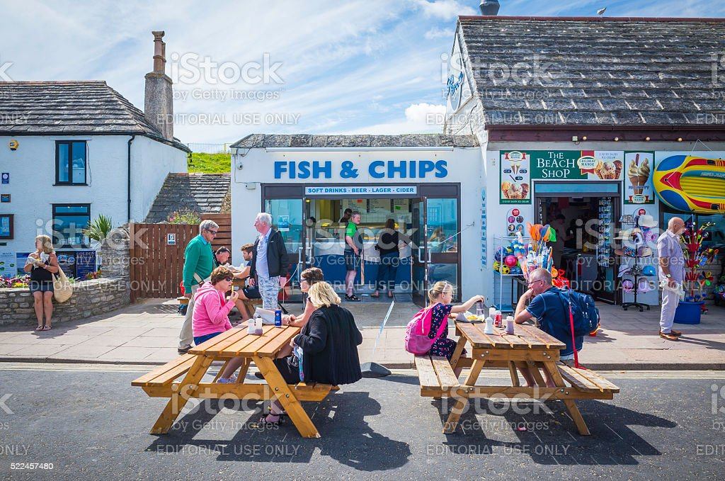 Tourists enjoying fish and chips at seaside resort Dorset UK stock photo