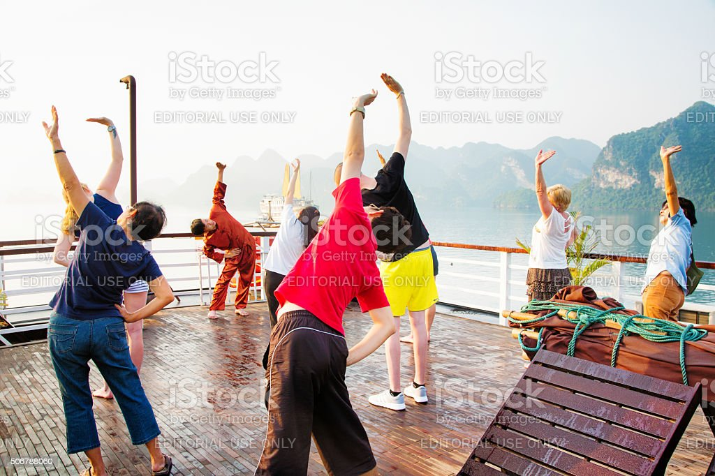 Tourists exercising while on Halong Bay cruise in Vietnam stock photo