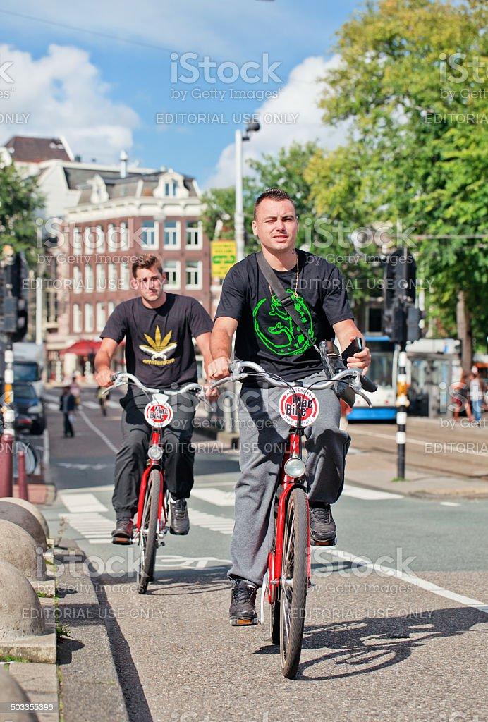 Tourists explore Amsterdam center on Mac Bike rental bicycles stock photo