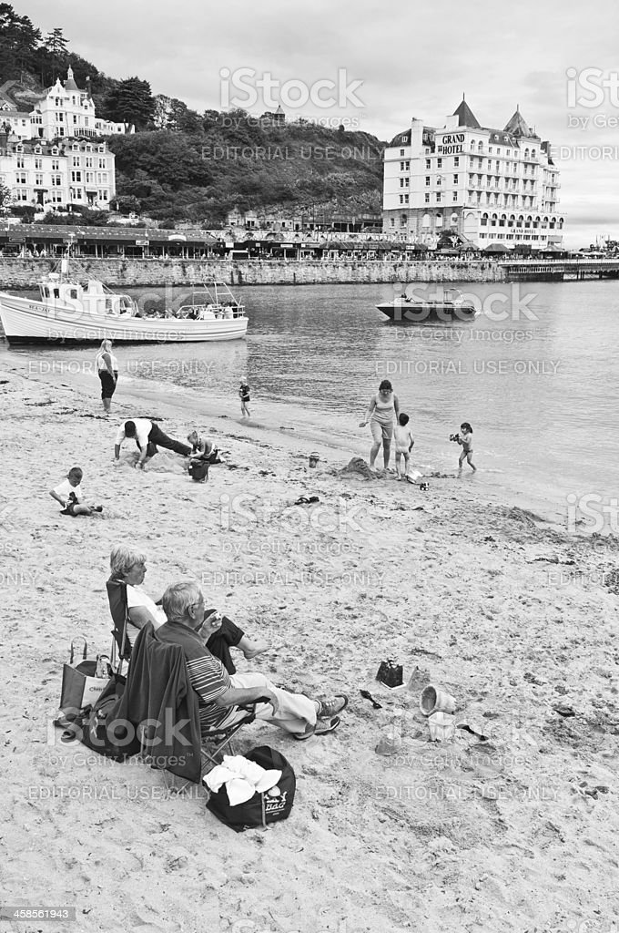 Tourists families relaxing on beach beside seaside royalty-free stock photo