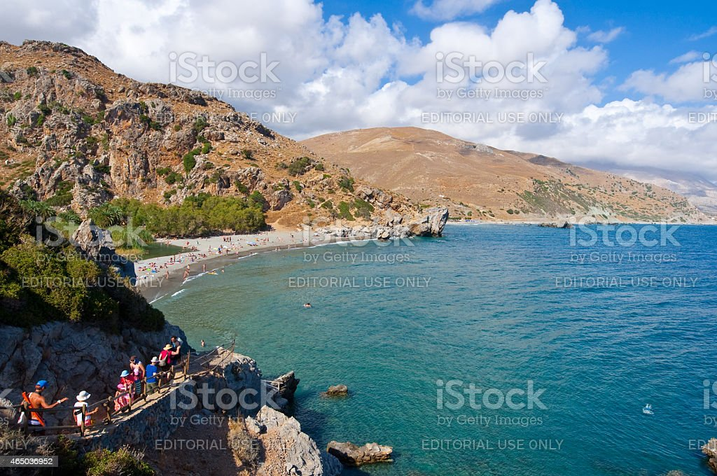 Tourists go down the steps to the Preveli Beach, Greece. stock photo