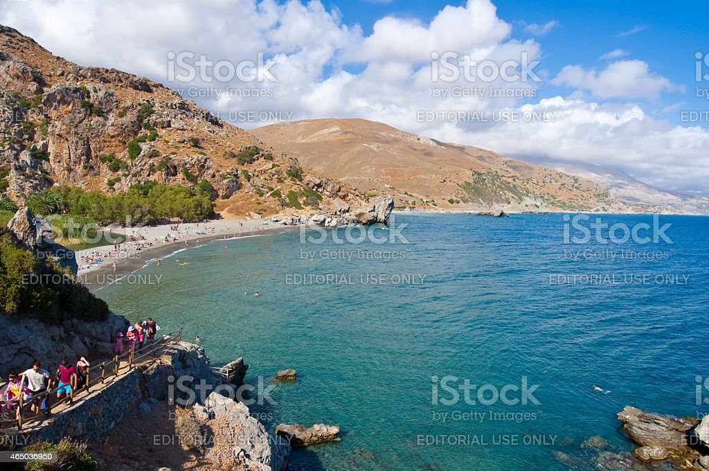 Tourists go downstairs to the Preveli Beach on Crete,Greece. stock photo
