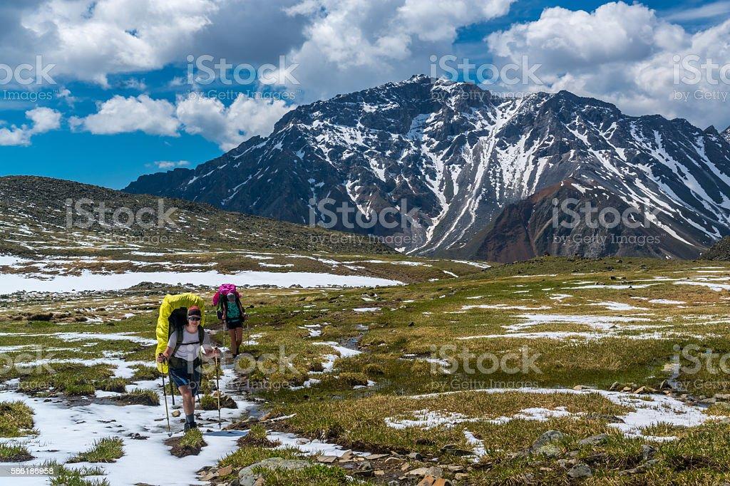 Tourists go on snow-covered alpine meadows in tunka range stock photo