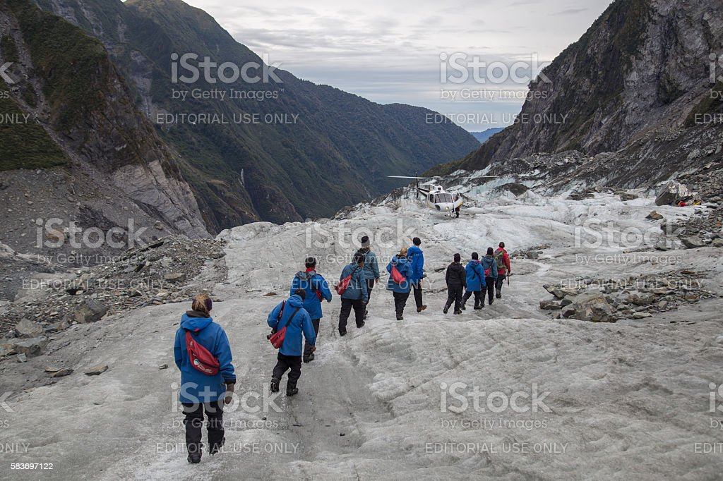 Tourists hiking on Franz Josef Glacier, New Zealand stock photo