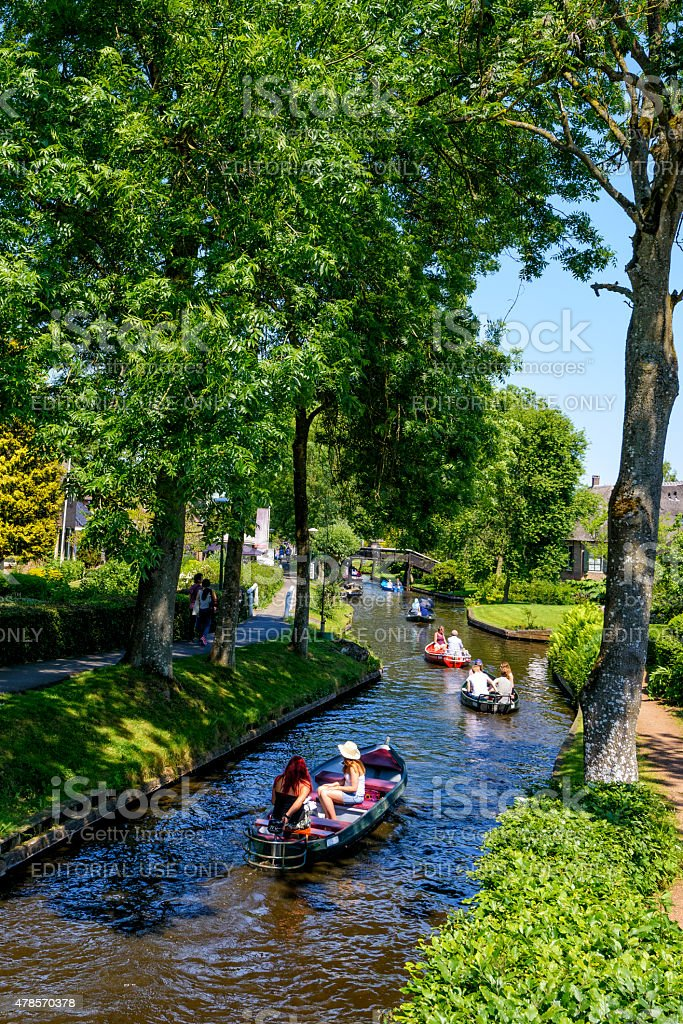 Tourists in a boat on the canal in Giethoorn stock photo