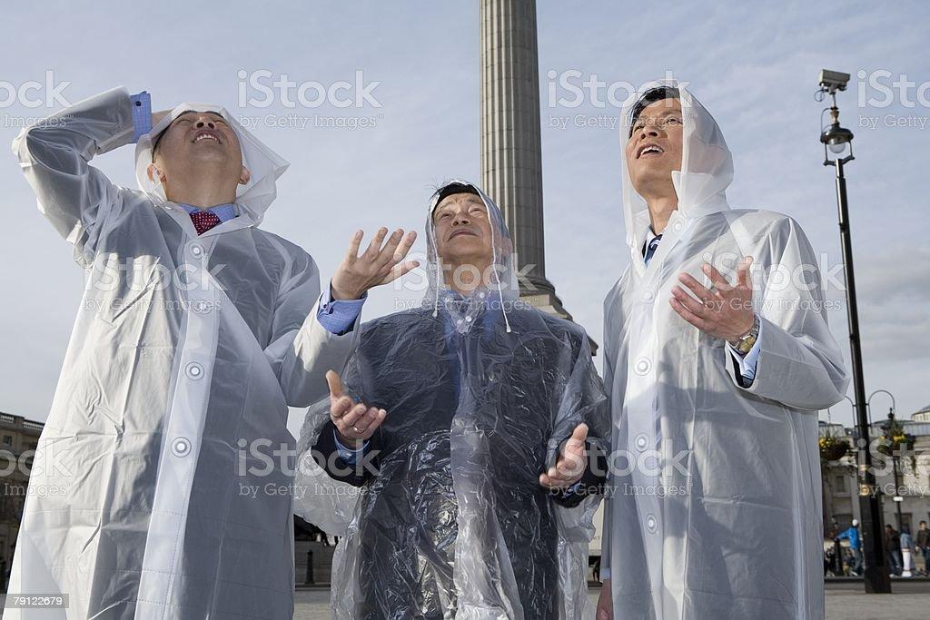 Tourists in raincoats stock photo