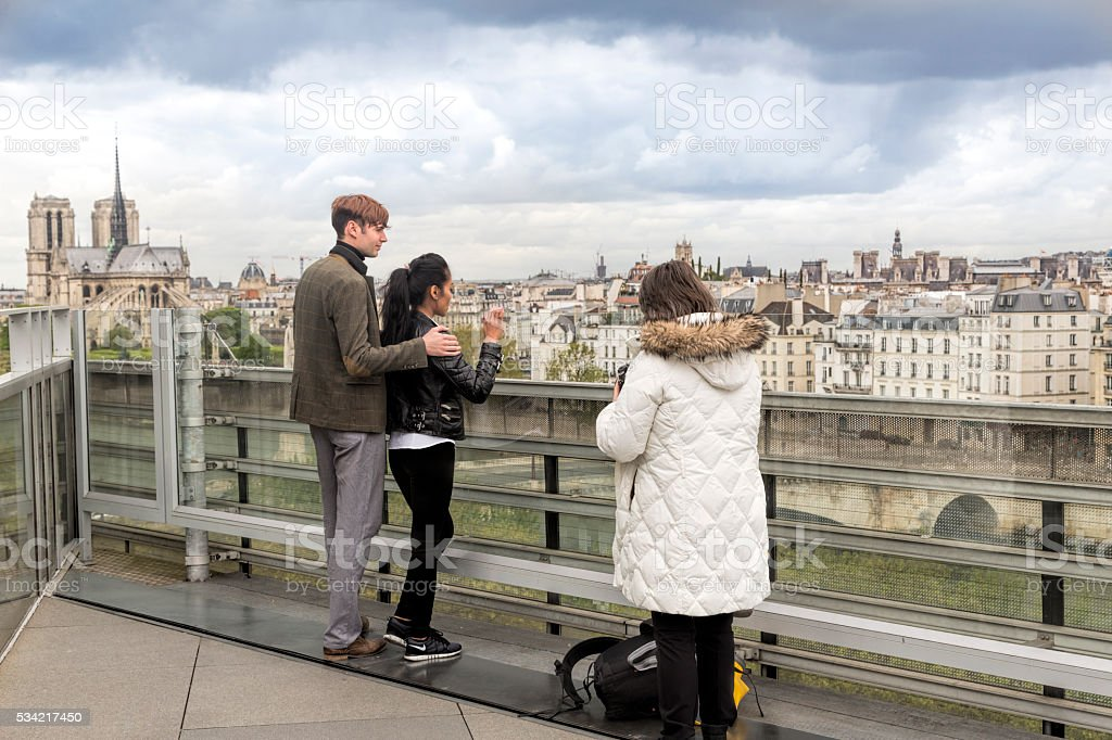 Tourists loking out over Paris with Seine and Notre Dame. stock photo