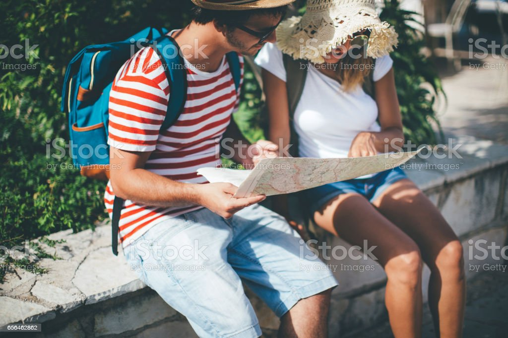 Tourists looking at city map stock photo