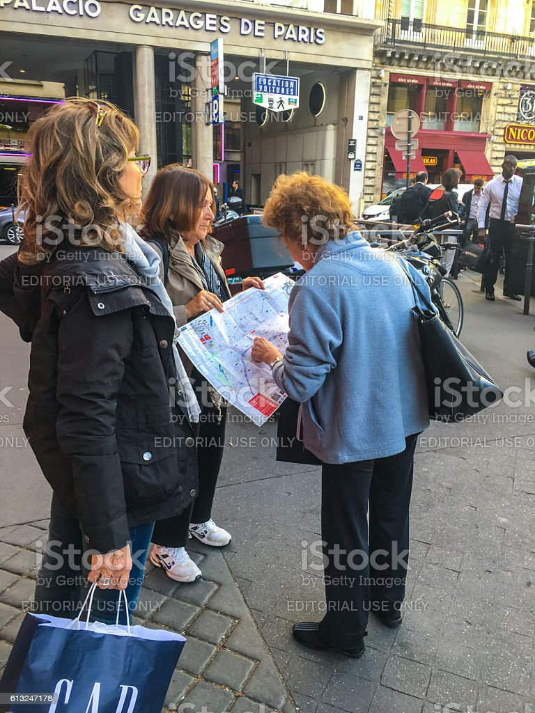 Tourists looking at Paris city map, France stock photo