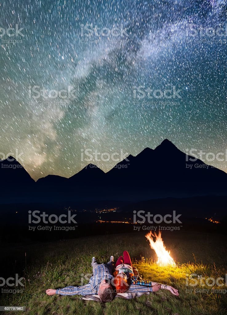 Tourists lying near the campfire under incredibly beautiful starry sky stock photo