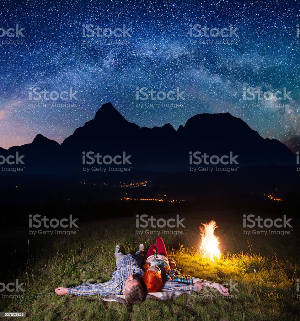 tourists lying under incredibly beautiful starry sky stock photo