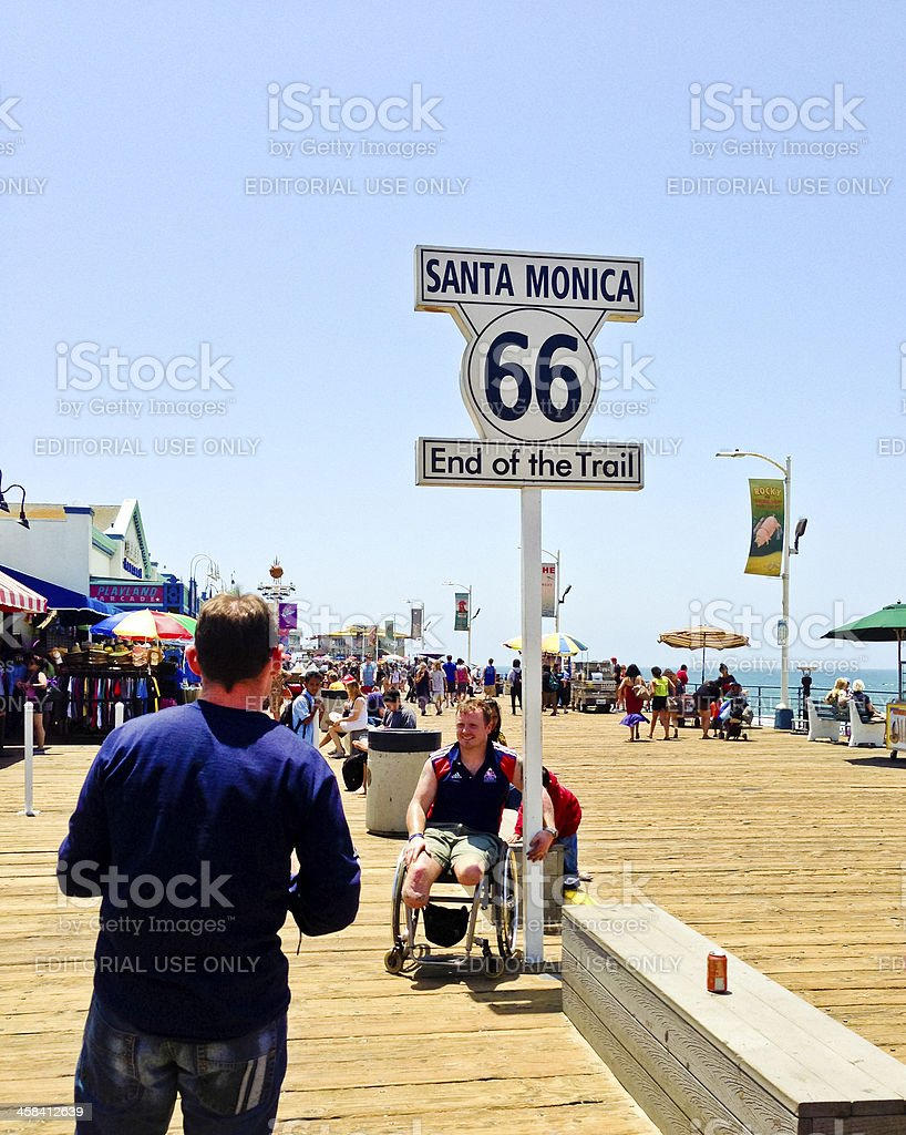 Tourists making photos with Famous Sign on Santa Monica Pier royalty-free stock photo