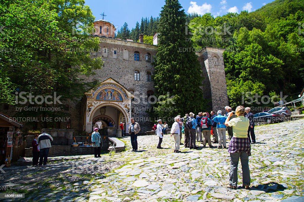 Tourists near the entrance arch of famous Rila Monastery, Bulgaria stock photo