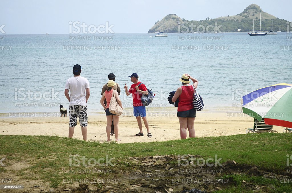 tourists on beach asking local for directions and information stock photo