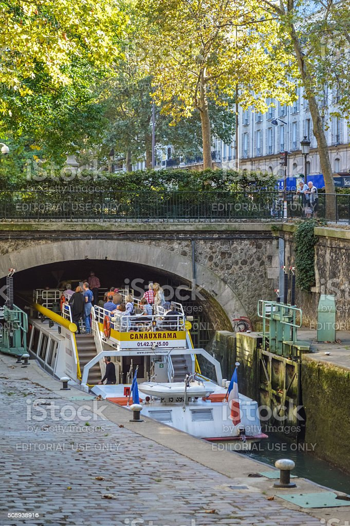 Tourists on boat at canal Saint-Martin in Paris stock photo
