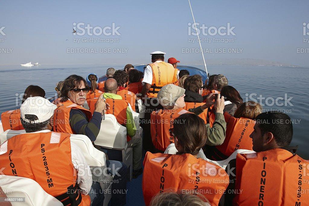 Tourists on boat excursion wearing orange lifejackets royalty-free stock photo