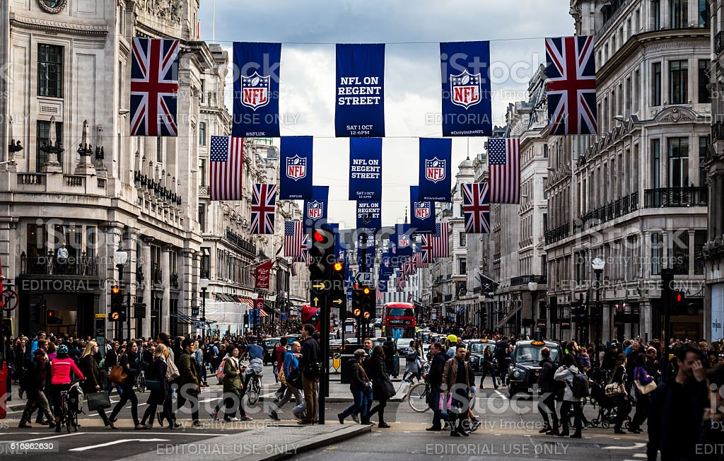 Tourists on busy Regent Street, London, with NFL flags stock photo