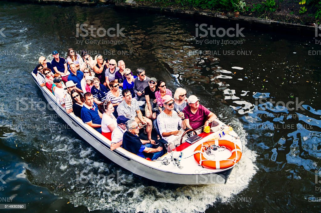 Tourists on canal boat in Bruges stock photo