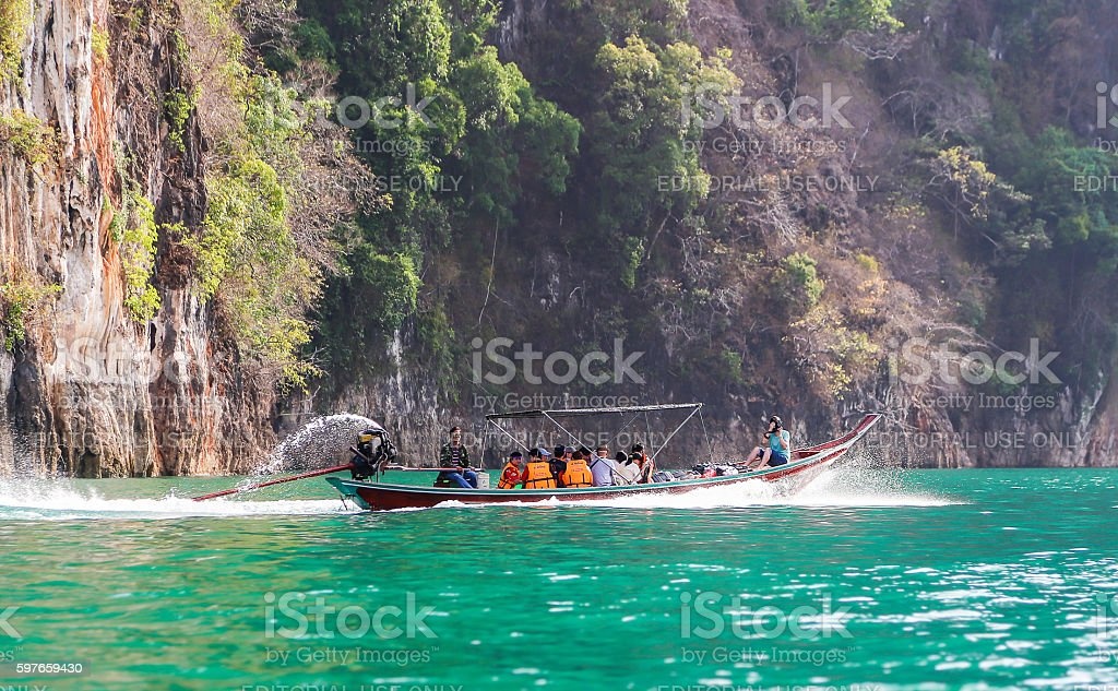 Tourists on long trail boat on green water surface stock photo