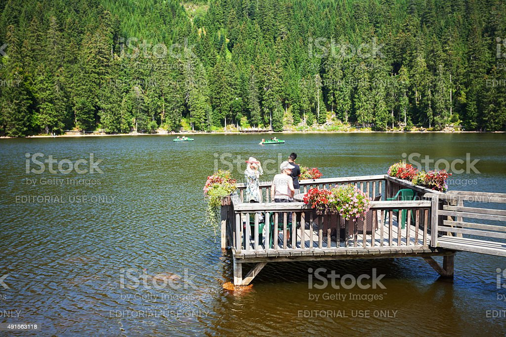 Tourists on pier in lake Mummelsee stock photo